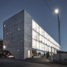 Cracks in the concrete facade of this office block in Aarhus by Danish architecture practice Sleth provide glimpses of the building's illuminated interior