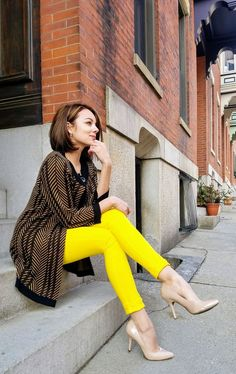 Yellow jeans, nude pumps, and a black and brown cardigan.