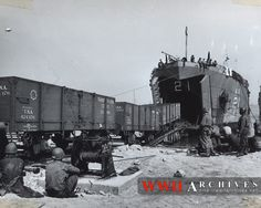 World War II Photograph: From the big mouth of a Coast Guard-manned LST, freight cars of the Army Transportation Corps pour onto a railroad in France after being ferried from England.  Equipped with rail tracks on the tank deck, the big tank landing ship serves as a floating link between railways in Britain and France, helping to expedite the flow of supplies to Allied armies on the Western Front.