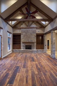 Contemporary rustic home - Living room with reclaimed wood floors, old beams, stone, vaulted ceiling. | Country Structure Custom Homes