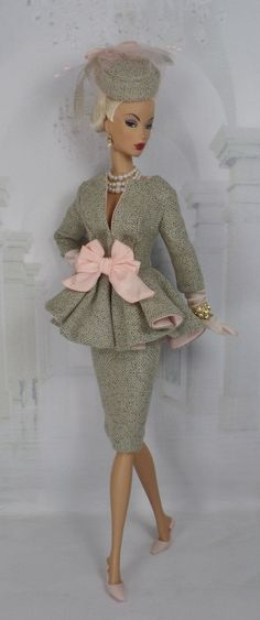 A formal suit cut from clay wool tweed features a jacket with three-quarter length sleeves, flaring peplum lined in contrasting blush silk with