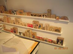 I used a channel for siding (found at big box stores) glued/screwed to the wall to organize my rubber stamps in my craft room.