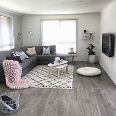 Industrial Design Living Room Shelving Ideas - In the picture, there is an old gray ash sofa with several pillows, a white oval table with underneath a black-and-white carpet #industrialdesignlivingroom #industrial_design_living_room #designlivingroom #industrialdesign