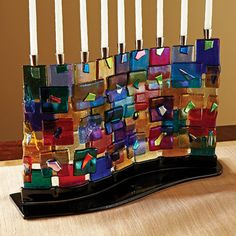 """Mosaic Fused Glass Multi Color Wall Menorah By Tamara Baskin.  Light-spreading and light-catching mosaic assemblage of rainbow colors in fused glass. The Western Wall menorah, as conceived and executed by this late Israeli artist, is a beautiful example of functional Judaic art to be enjoyed year round. Hand-made; each a unique work of art (13¾""""L x 8¾ x 3½)"""