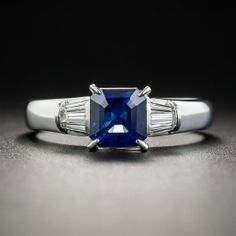A rich royal blue Ceylon sapphire, weighing 1.22 carats, fashioned with a striking square emerald-cut shape, radiates between fans of sparkling white baguette diamonds, all presented in gleaming platinum. A chic and stunning modestly proportioned estate jewel, currently ring size 6 1/4.