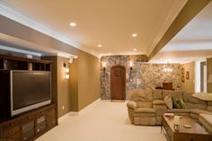 Large finished basement with big screen TV, sectional sofa, rock wall and recessed lighting