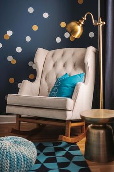 Gold and blue boy's nursery features an accent wall painted Benjamin Moore Hudson Bay lined with silver and gold dot wall decals, Land of Nod Lottie Dot Decals, lined with a tufted wingback rocker, Empire Rocker, and a West Elm Martini Side Table as well as an aqua knitted pouf illuminated by a brass floor lamp placed in front of a window dressed in navy curtains.