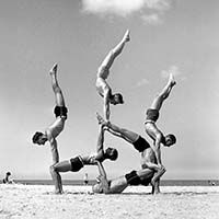 In this six-man ground pyramid (from left to right, top row) Wal Balmus, Frank Cottier and Max Stewart hand-balance off Vic Whitehead and Jack Goldberg (face obscured), all supported by bearer Alf Stanbrough.    The Graham gymnasts also gave many free displays and exhibitions at various orphanages and institutions for those unable to see their stunts on Bondi Beach.    16 April 1939