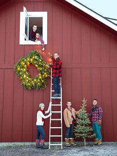 Farm Chicks founder Serena Thompson and her family adheres a string of lights to their barn's oversized wreath.
