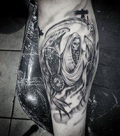Grim Reaper tatuagem com asas. O reaper tem asas e é, ao mesmo tempo, acompanhado por um black raven. Em suas mãos, você também pode ver um relógio para contar o restante momentos de almas que estão prestes a morrer.