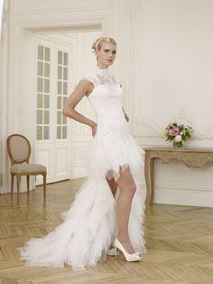 BIZET: Robe de mariée courte devant et longue derrière. Buste en dentelle cornélie. Décolleté transparent fermé effet cache-épaules boutonné dans le dos à manches courtes. Belle jupe et longue traine en dentelle recouvertes de mouchoir de tulle.