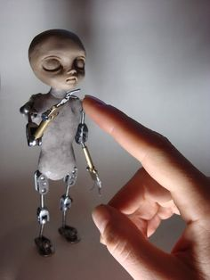 This little guy looks like he was built mechanically. Using little pieces of mettle and bolts to give the character movement when filming.  I am not sure what the body is, maybe wood or clay. The head looks like rubber.