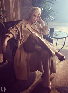 Emily Blunt poses in tan trench coat, pants and pumps