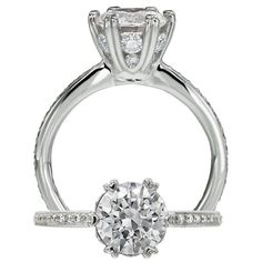 Ritani Setting diamond ring featuring a prong set round cut centerstone that is surrounded by microset diamonds within the mini heart prong setting.  Finishing this ring is the single row micropavé shank.