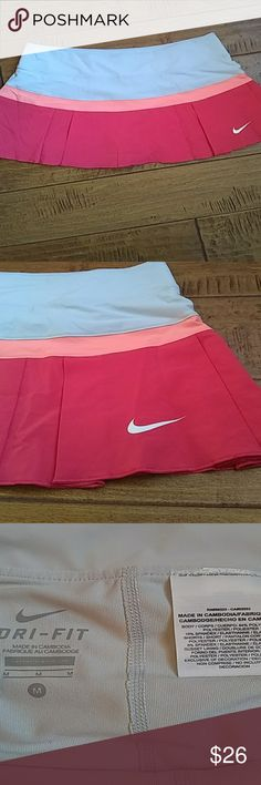 Nike tennis skirt Nike Tennis Skirt Like New For (Female) Size (Medium) Color (silver) (orange) (pink) DRI-FIT Made in Cambodia 84% POLYESTER 16% SPANDEX Has the Nike logo on the front lower left of the skirt. The skirt has shorts underneath. Nike Skirts Mini