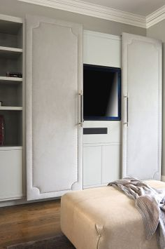 TV hidden behind sliding upholstered doors in a home in London designed by Susan Knof