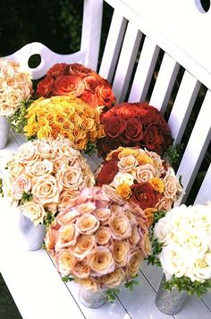 Bouquets of roses, a different color for each bridesmaid.