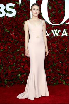 Saoirse Ronan looks elegant in a Stella McCartney rose-pink gown with peephole detail, gold box clutch, and satin platform shoes on the Tony Awards red carpet.