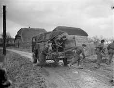 Troopers of a Canadian armoured brigade getting out of a new GMC fifteen-hundred weight armoured truck near Nijmegen, Netherlands, 5Dec1944.