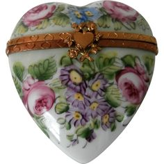 This very charming Limoges box is made of hand painted China and opens to reveal two tiny perfume bottles. It's heart shape makes it the perfect gift