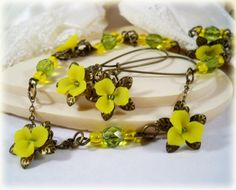 """Antique brass, olive and yellow set the tone to this vintage style jewelry. Lots of my little 3-petal yellow flowers are along this necklace. Each flower is backed by a decorative bronze cap on a matching 2mm brass chain. Adoring Czech glass faceted beads for a final touch. Little flowers are approx. 1/2"""" and pendant measures 1"""". Wear as a choker or longer. 14"""" necklace + 2"""" adjustable chain.    Matching flower earrings on long antique brass earwires approximately 5 cm long."""
