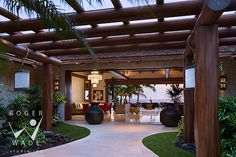 dining lanai looking towards terrace, infinity pool and Pacific Ocean at twilight, luxury timber frame Hawaiian home