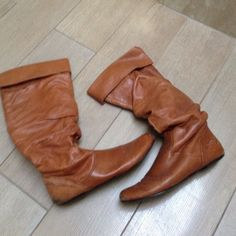 Tan Boots Have been worn, there is wear shown in the back heels and some on the front. The dark spot shown in the photograph is just part of the style of the boot and the material. It is not from damage. Shoes