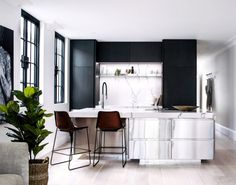 The kitchen is a real stunner with beautiful crisp black cabinets that add a designer touch and a wonderfully modern island that is the central feature in the open plan area. Complete with bespoke bar stools, marble finishes and stainless steel – the room is contemporary and oh so cool.