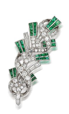 A diamond and emerald brooch, Tiffany & Co.  of foliate motif, detailed with calibré-cut emeralds and baguette-cut diamonds, further accentuated by a ribbon of round brilliant-cut diamonds; signed Tiffany & Co; estimated total diamond weight: 2.50 carats; mounted in platinum; length: 2 1/4in.