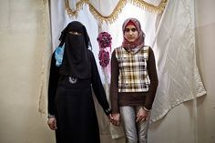 """Tanya Habjouqa, Wives of the Syrian Revolution, 2012-2013. Photograph. """"Layla and Sama …Their mother, Um Muhammad, 39, says life is hard without her fighter husband. The mother of six is struggling to secure the monthly rent and is under constant pressure to marry off her daughters to Jordanian and Syrian suitors. Layla, right, was trampled upon in her sleep when an army unit stormed their house looking for their father before they fled to Jordan."""" Interview by Cecilia Andersson."""