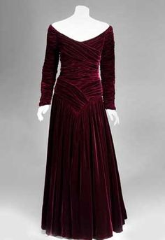 Designed by Catherine Walker. Burgundy velvet ball dress with gathered bodice  and skirt and long sleeves with rouleaux down the outside arm...