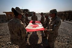 Canadian Army soldiers of the 22nd royal regiment, 1st battalion, Bulldog company, 1st platoon, fold the Canadian national flag during a ceremony marking the Canadian handover of forward fire base Zangabad to U.S. forces. (Baz Ratner/Reuters