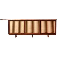 1stdibs | Natural Edge Credenza By George Nakashima in Walnut and vertically slatted Pandanas Cloth-backed sliding doors, ca.1985