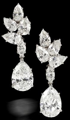 pair of diamond pendant earrings, Harry Winston. each designed as a pear-shaped diamond, weighing 3.90 and 3.43 carats, suspended from a marquise-shaped diamond and a cluster surmount of pear-shaped diamonds; unsigned, no. 6439, with signed box; remaining diamonds weighing approximately: 5.50 carats total.