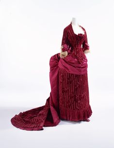 1883, France - Reception dress by Charles Frederick Worth - Wine-red silk satin cut velvet with stripes and leaf pattern; figured additional cut velvet layer on leaf pattern; set of bodice and skirt with bustle; tulle and silk satin bows at cuffs; apron-shaped overskirt draped toward back