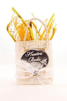 """A small gold ribbon filled bag party favor for weddings. The silver label on the bag has the occasion printed on it, """"Nuestra Boda"""" which translates to """"Our Wedding""""."""