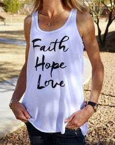 "This ultra-soft white Christian tank top for women (racerback) features ""Faith Hope Love"" on the front in a beautiful black script. ""But now faith, hope, love, abide these three; but the greatest of these is love."" - 1 Corinthians 13:13"