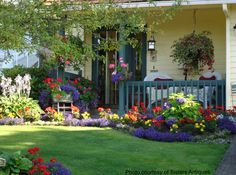 This front yard is packed with vibrant color. Isn't that what makes this landscaping so appealing? Front-Porch-Ideas-and-More.com #frontyard landscaping #porchlandscaping #landscapingideas