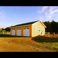Three Car Garage by North Country Sheds. This custom garage includes board and batten siding, three garage door, one man door, double sliding barn door, concrete floor, heated water supply, and an electrical package. Visit NorthCountrySheds.com