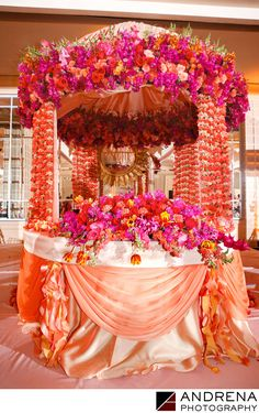 ANDRENA PHOTOGRAPHY - Beverly Hilton Wedding Photograph: Asiel Design partnered with Nikki Khan at Exquisite Events to create this unique sweetheart table out of the ceremony mandap. It was a creative way to reuse the ceremony flowers for the reception, and this image has been published in several books and magazines, including Art of Celebration Los Angeles and South Asian Bride magazine. The combination of peach, orange, fuschia was truly beautiful, and it is rare to see a sweetheart…