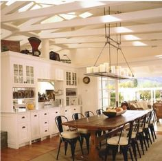 Here's a fabulous country cottage style kitchen with white wood beam ceilings and a breathtaking candle chandelier.