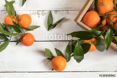 Tangerines with leaves on white wooden table background.