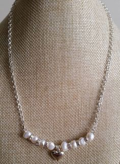 Set on a 4mm silver-toned rollo/belcher chain, the pretty white pearl and clear AB crystal rondelle spacer pendant features a silver toned puffed heart.