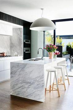 Îlot central en marbre et tabourets de bar en bois. #cuisine #moderne