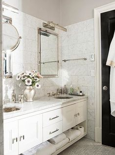 This master bath is a thoroughly modern masterpiece, revamped by silver finishes, a pair of octagonal sinks, and walls of Carrara marble tiles.