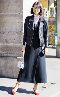 Leandra Medine wears a lace turtleneck underneath a black dress with a motorcycle jacket, ankle-strap ballet pumps, a white chain bag, and mirrored sunglasses