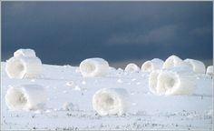 Snow rollers form when wet snow falls on ground that is icy, so snow won't stick to it. Pushed by strong winds, the snow rolls into logs.
