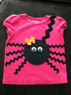 Spider shirt cuteness I just made! Glitter felt .25 cents, small ric rac for legs, large ric rac for string, eyes were .50 cents. Plain shirt I already had. Use fabric glue! Took about 20 minutes. Bow I already had.