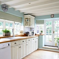A casual yet chic country feel has been created in this quaint kitchen with a mix of cream cabinetry, refreshing blue walls and a white beamed ceiling. Retro-style accessories add a sense of fun to the space