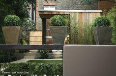 Минимализм функциональный и уютный… Этот современный сад с элементами минимализма (на заднем дворике дома) имеет простоту конструкции и привлекательный декоративный акцент.  Он предусмотрен как наружная комната для отдыха и развлечений. Сад имеет две отдельные зоны.  Конструкция из древесины имеет форму куба, по периметру которого размещены скамейки для отдыха. В отдельных местах куба размещены встроенные светильники из нержавеющей стали для темного времени суток. Прожекторы на боковой…